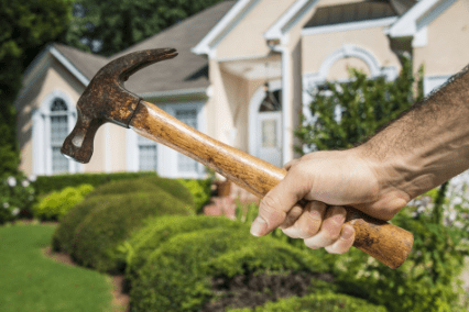 picture of hand holding hammer in front of a house